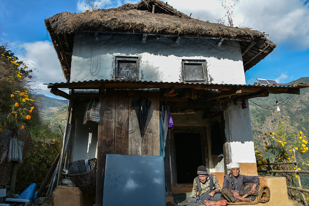 A gurkha veteran and his wife outside their house in Nepal