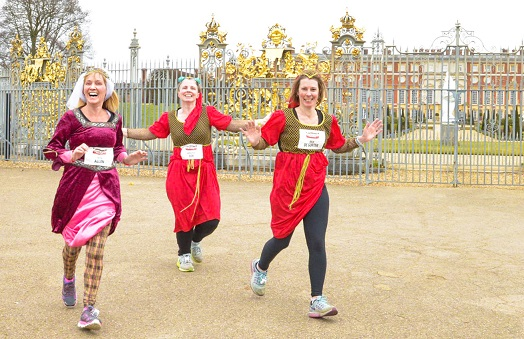 Three women running outside Hampton Court Palace wearing red historical costumes