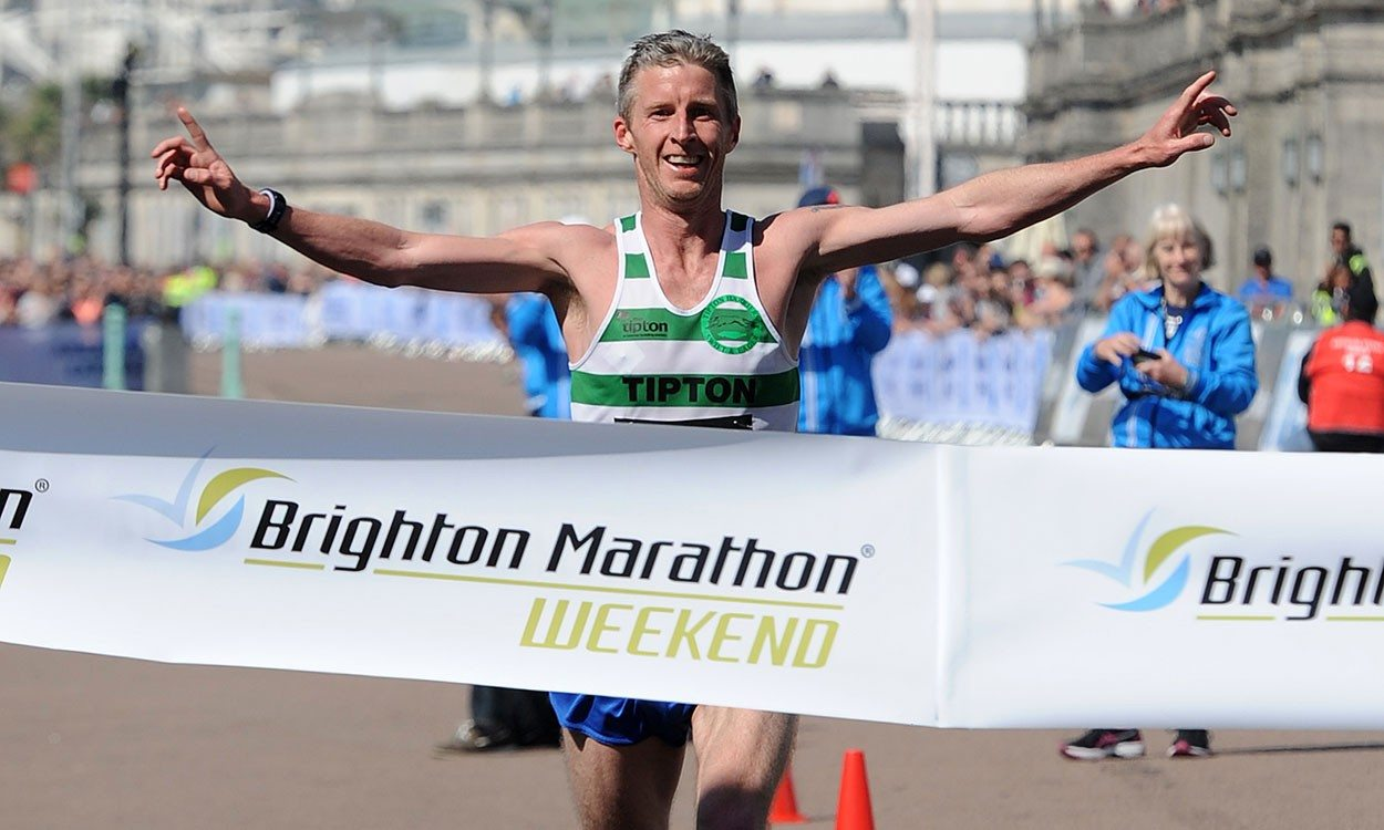 Man running through Brighton Marathon finish line