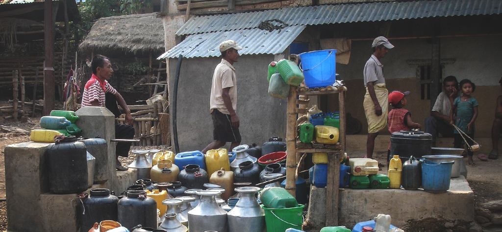 Poor villagers with empty colourful water containers