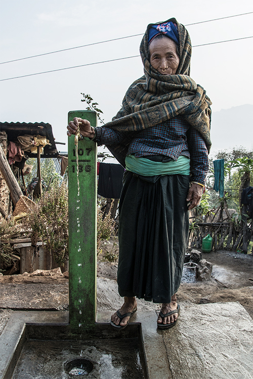 Elderly Nepali Widow Woman next to tap clean water