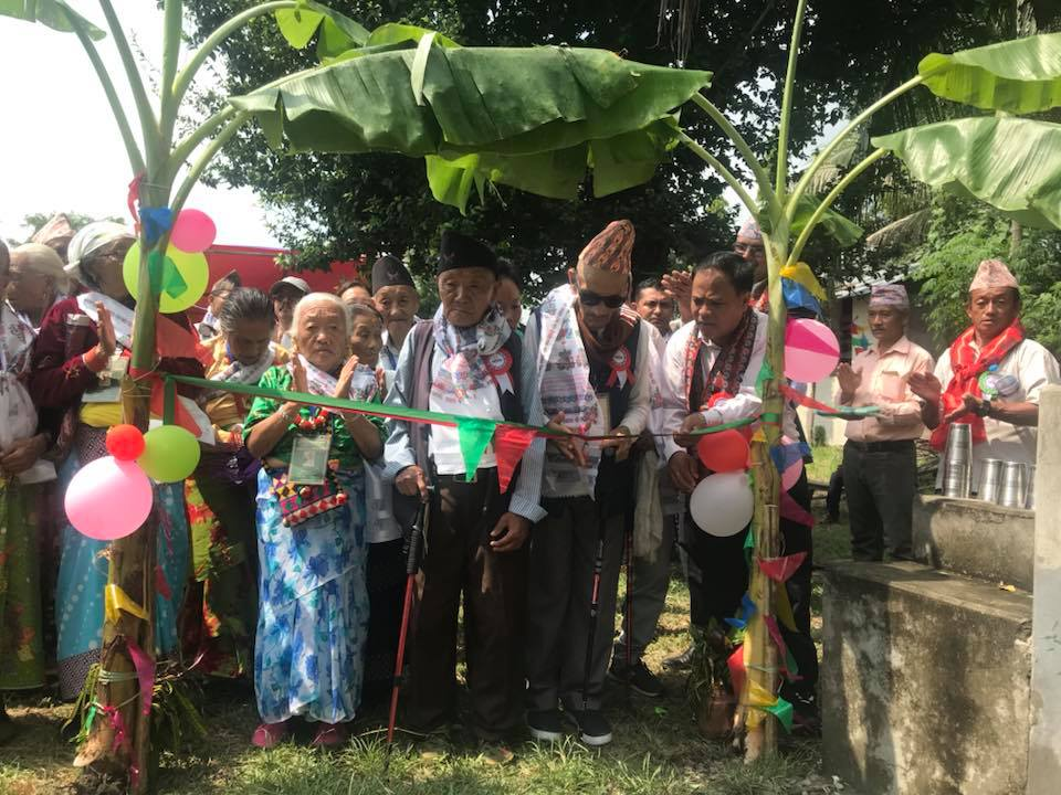 Elderly Nepali Gurkha veterans and widows standing in a group surrounded by trees and balloons. One of them is cutting a ribbon at a water project.