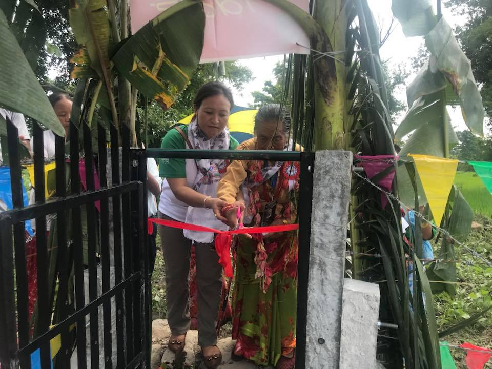 Elderly Nepali lady cutting a red ribbon to unveil a water project.